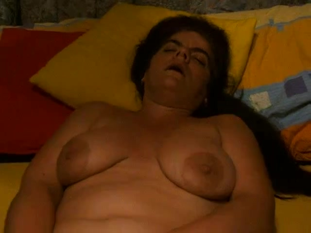 Busty mature smacks herself with a red dildo