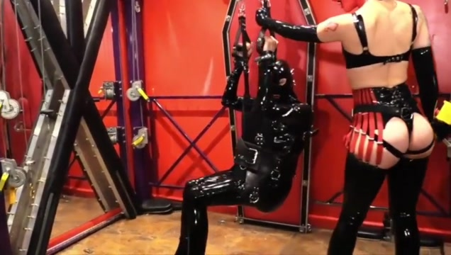 Red masked rubber mistress fucks latexslave ass