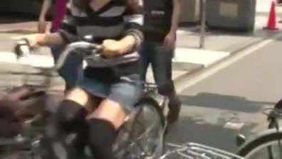 Japanese girl rides a bike with short skirt in streets